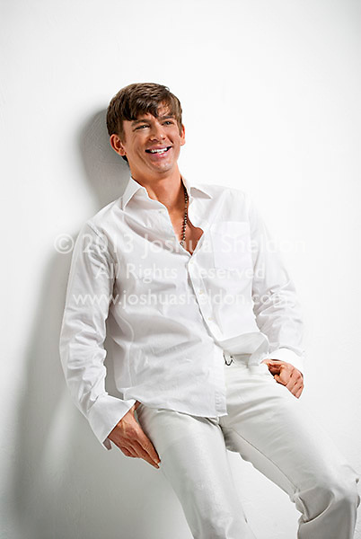 Smiling young man leaning against white wall