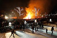 Nederland Amsterdam 2015 01 03. Jaarlijkse Kerstboomverbranding op het Museumplein. Op de voorgrond schaatsen mensen op de ijsbaan