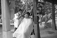 Barber cutting hair under his house whith a cow in background<br /> on, Kaoh Trong, island,<br /> ,Kratie, Cambodia,<br /> October 2020.