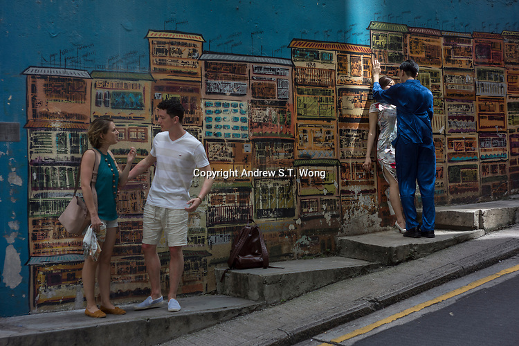 Mid-Levels, Sheung Wan District, Hong Kong - Tourists in front of a mural, June 2017.