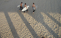The shadow from Huntington Beach Pier hangs over surfers walking along the beach.