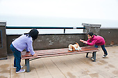 Lima, Peru. Miraflores district, Larcomar Mall. Two young girlfriends (Peruvian) slide a stuffed animal back and forth on a bench at a viewpoint over the Pacific Ocean. No MR. ID: AL-peru.