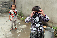 Tibetan children play in their home on the Tibetan Plateau, in western China. Relocation communities been created to house nomadic herders moved from the highland grasslands. The nomads have been blamed for contributing to the deterioration of the grasslands, so have been moved, sometimes forcibly, into newly built towns that can be found across the plateau.
