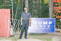 A security guard stands near a Trump/Pence campaign sign before the arrival of Donald Trump, Jr., son of president Donald Trump and a rising Republican political star, at an outdoor campaign rally at The Lobster Trap in North Conway, New Hampshire, on Thu., Sept. 24, 2020.
