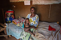 AWright_SUD_000592.jpg<br /> South Sudan<br /> Silvia Aja holds her seven-month-old, who is recovering from malaria, in her home outside Juba. Silvia has four children and has lost three. They are now visited regularly by a BRAC community health worker.