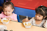 Education Preschool Phase-in First Days of School 2s program two girls feeding themselves at breakfast