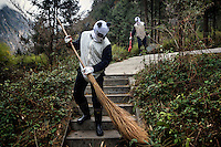 Researchers dressed in panda costumes clean one of the wild panda enclosures at the Hetaoping Panda Conservation Centre. The researchers wear the panda costumes to prevent the wild pandas from becoming accustomed to humans.