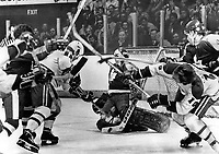 1970 FILE PHOTO - ARCHIVES -<br /> <br /> Under Attack: Leafs goalie Mike Palmateer is surrounded by flailing sticks and falling bodies during Stanley Cup semi-final game at Montreal. On this play; Palmateer managed to hold off Habs Steve Shutt (22) and Guy Lafleur (10); while Leaf Trevor Johansen (4) searches for puck. Habs dumped Leafs; 3-2; to take 2-0 series lead; which switches to Gardens for next games; Saturday and Tuesday. Leafs say they'll do better.<br /> <br /> PHOTO : Graham Bezant - Toronto Star Archives - AQP