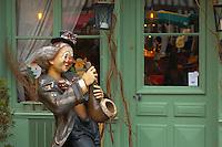 Clown figure playing a Saxaphone outside a restaurant. Honfleur, Normandy, France.