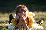A young pioneer girl laying in the grass with a daisy flower