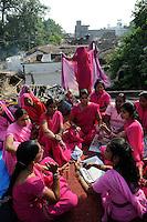 INDIEN Uttar Pradesh, Bundelkhand, Frauen unterer Kasten und kastenlose Frauen organisieren sich in der Frauenbewegung Gulabi Gang von Sampat Pal Devi , sie fordern gleiche Rechte und kaempfen notfalls mit Gewalt mit Bambusstoecken gewalttaetige Maenner, Korruption und Polizeiwillkuer , Zeitungsschau, Lagebesprechung und Planung einer Demo in Mahoba / INDIA UP Bundelkhand, women movement Gulabi Gang in pink sari fight for women rights and against violence of men, corruption and police arbitrariness, meeting in Mahoba