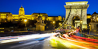 Szechenyi Chain bridge, stone lions, and royal palace lit up during twilight, with colorful light trails from car traffic, Budapest Hungary