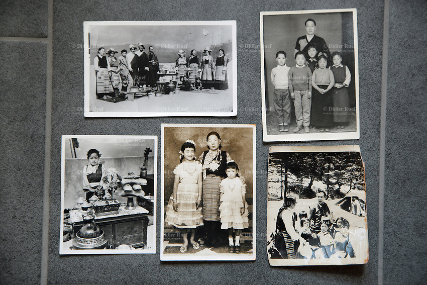 "Switzerland. Canton Aargau. Brugg. Yangchen Büchli and black and white pictures from her childhood in Tibet. On the bottom right corner, the picture shot before her departure and depicting her as child with the young Dalai Lama. The swiss tibetan woman is an Aeschimann's child who arrived 50 years ago in Switzerland to receive custody on a private initiative by an influential Swiss industrialist, Charles Aeschimann. In 1962, Charles Aeschimann agreed with the Dalai Lama to take 200 children and place them in Swiss foster homes and give them a chance for a better life and a good education. Most of the children still had parents in exile or in Tibet, just a few were orphans. The 14th and current Dalai Lama is Tenzin Gyatso, recognized since 1950. He is the current Dalai Lama, as well as the longest-lived incumbent, well known for his lifelong advocacy for Tibetans inside and outside Tibet. Dalai Lamas are amongst the head monks of the Gelug school, the newest of the schools of Tibetan Buddhism. The Dalai Lama, also called "" Ocean of Wisdom"" is considered as the incarnation of Chenresi, the Bodhisattva of compassion who is also the protective deity of Tibet. 25.02.2015 © 2015 Didier Ruef"
