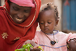 Haoua Pendooru, a Fulani woman in Ouagadougou, Burkina Faso, prepares a sald as her young daughter looks on.