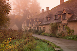 United Kingdom, England, Gloucestershire, Cotswold, Bibury: Arlington Row cotswold cottages in autumn fog | Grossbritannien, England, Gloucestershire, District Cotswold, Bibury: typische Haeuschen, Arlington Row im Herbstnebel