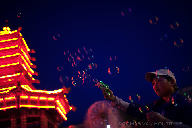 A girl makes bubbles near the neon lit pagoda in Lenin square in Elista, Republic of Kalmykia, Russian Federation on May 6, 2010.