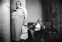 England. Greater Manchester. Salford. Women living in poverty. Alice (R) is 60 years old. She is a widow and lives alone in a flat in a council house with her retirement pension. Her friend is standing up and holds in her left hand a plastic bag from Woolworth. Woolworths Group, former operator of the Woolworths chain of shops in the UK, ceased trading and liquidated in early 2009. Salford is a city in the Metropolitan Borough of Salford in Greater Manchester. North West England is one of nine official regions of England. © 1990 Didier Ruef