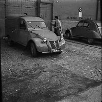 """Affaire de la """"Tournerie des drogueurs""""  JUIN 1961<br /> <br /> Devant l'entrée de la prison Saint-Michel. 3 juin 1961. Plan moyen de l'entrée de la prison (vue de 3/4 face) ; une 2CV fourgonnette est stationnée devant, deux hommes sont à côté. Cliché pris dans le cadre de l'affaire de la """"Tournerie des drogueurs"""" dont le procès s'est ouvert à Toulouse le 5 juin 1961. Observation: Affaire de la """"Tournerie des drogueurs"""" : Procès qui s'est ouvert aux assises de Toulouse le 5 juin 1961, sous la présidence de M. Gervais (conseiller doyen). Sur le banc des accusés se trouvent François Lopez, Raoul Berdier, Marie-Thérèse Davergne (Maïté) et d'autres malfaiteurs toulousains (Camille Ajestron, Henri Oustric, Raymond Peralo, Marcel Filiol, Paul Carrère, Charles Davant et François Borja). Outre les accusations pour association de malfaiteurs, ils comparaissent pour l'assassinat de Jean Lannelongue, propriétaire du Cabaret la Tournerie des Drogueurs (rue des Tourneurs) dans la nuit du 3 au 4 janvier 1959, au cours d'une tentative de racket."""