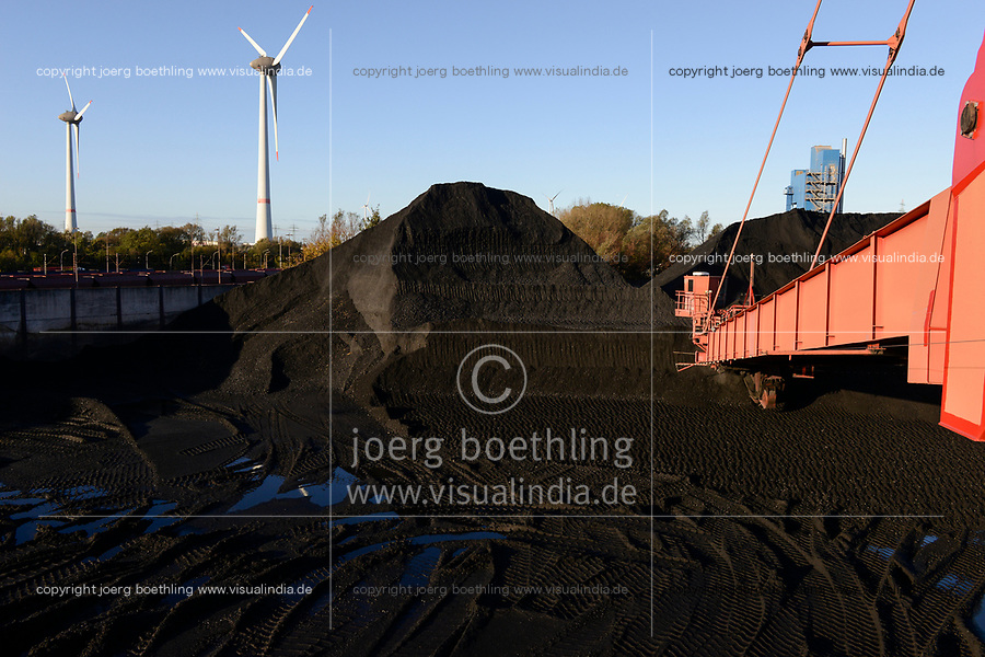 Germany, Hamburg, Hansaport import of coal and ore for steel plants and coal power stations, storage place in contrast with wind turbine in harbour / DEUTSCHLAND, Hamburg, Hansaport, Import von Kohle und Erz, Lagerung und Weitertransport zu Kraftwerken und Stahlwerken
