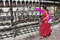 Kathgmandu, Nepal.  Nepali Woman Spinning Prayer Wheels at Swayambhunath Temple.