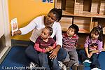 Education Preschool 3 year olds female teacher reading to small group of children horizontal