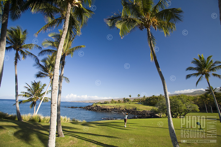 Man playing golf at an oceanfront resort on the leeward coast of the Big Island of Hawaii