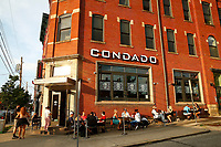 Patrons dine outside of Condado in the Lawrenceville neighborhood while others wait for to-go orders on Tuesday July 21, 2020 in Pittsburgh, Pennsylvania. (Photo by Jared Wickerham/Pittsburgh City Paper)