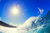 Bodyboarding off the wall of a large wave on the north shore of Oahu.