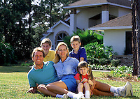 Smiling young family portrait in front of a house.