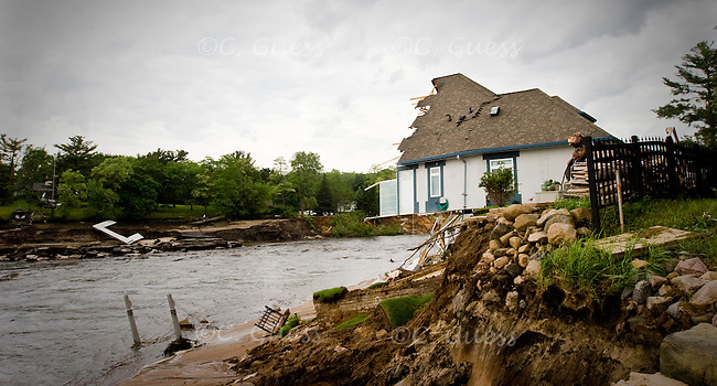 One of the houses that used to sit on the land that Lake Delton destroyed when it subverted its dam sits cut in half above a fifteen foot deep trench.