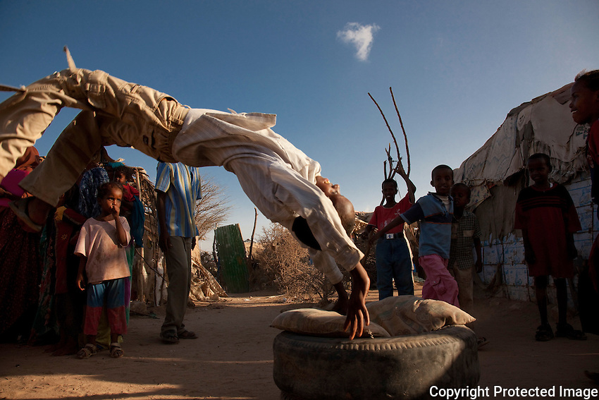 Children using an old tire and pillow as a makeshift trampoline to do flips in the shadow of State House in Hargeysa, Somaliland..
