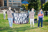 """A crowd gathers in Boston Common for the 2020 Women's March protest in opposition to the re-election of US president Donald Trump in Boston, Massachusetts, on Sat., Oct. 17, 2020.<br /> The sign here reads """"Black Lives Matter."""""""