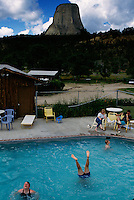 Tourists cool off in a swimming pool located under Devil's Tower an ancient volcano plug  or monolithic igneous intrusion that is more than 1200 feet high. It was featured in the Hollywood movie Closer Encounters of the Third Kind in 1977.
