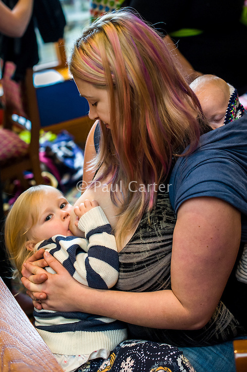 A mother breastfeeds her two year old daughter with her twelve week old baby asleep in a sling on her back.in the family restaurant and play area of a pub.<br /> <br /> Lancashire, England, UK<br /> <br /> Date Taken:<br /> 07-01-2015<br /> <br /> © Paul Carter / wdiip.co.uk