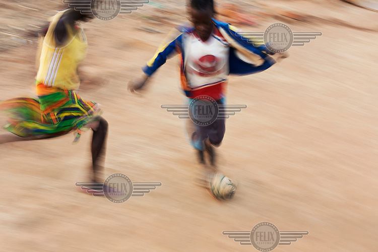 Choice (8) and Sherie (11) play football with a ball made from tightly bound plastic bags.