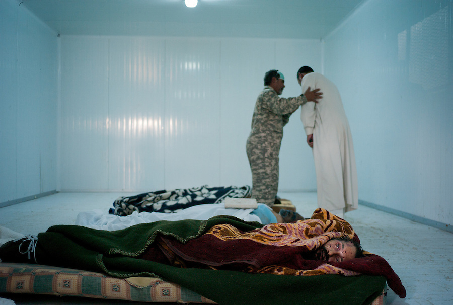 Libyan men view the body of Muammar Gaddafi lying in a commercial freezer at the African Tunisian Souq in Misrata, Libya, Saturday October 22, 2011. The confirmed death of Muammar Gaddafi brings closure to an 8 month uprising turned revolutionary war.