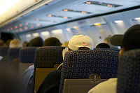 Traveler's hat with an embroidered American flag sewn onto the back side, sits in an airline seat awaiting takeoff.