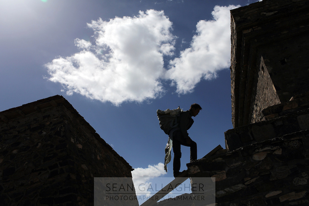 A Tibetan man climbs up to a stupa against blue and white skies on the Tibetan Plateau, in western China.