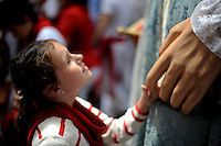 A young gild shakes the hand of a man dressed as a giant during the giants and big heads parade of the San Fermin festival, on July 10, 2012, in the Northern Spanish city of Pamplona. The festival is a symbol of Spanish culture that attracts thousands of tourists to watch the bull runs despite heavy condemnation from animal rights groups(c) Pedro ARMESTRE