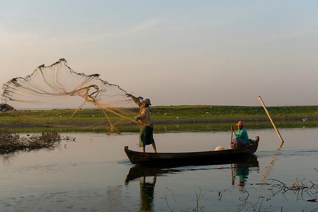 A fisherman in his boat next to U Bein Bridge at Taungthaman Lake near Amarapura, Mandalay, Myanmar is throwing his net.
