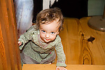 Small brunette  1+ girl holds bannister on stairway to begin climbing and crawling up stairs in house