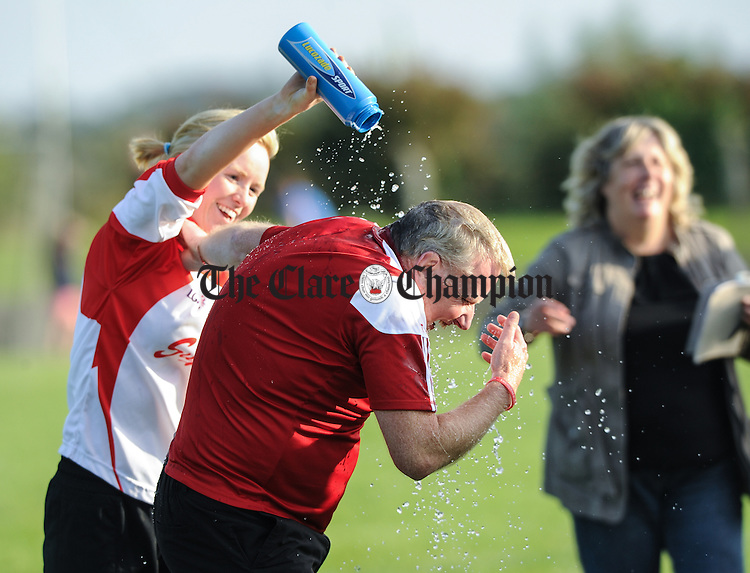 The Eire Og team manager gets a soaking from goalie Aoife O Neill  on the final whistle following their Junior Football county final win over Kilrush at Doonbeg. Photograph by John Kelly.