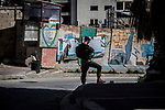An Israeli soldier stands guard in the West Bank city of Hebron before Jewish settlers start celebrating the Purim holiday in a parade, Sunday March 12 2017. Purim is a Jewish holiday that commemorates the saving of the Jewish people in ancient Persia , the story is recorded in the Biblical Book of Esther. Photo by Eyal Warshavsky