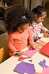 Education preschoool children ages 3-5 art activity two girls working on torn paper collages gluing or cutting paper vertical