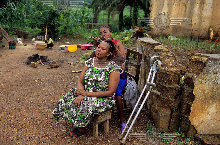 Fatmata Sisay, a hairdresser, with one of her clients. Fatmata had polio when she was one year old and has never been to school. The NGO Leonard Cheshire helped her to set up her own business. She charges 2,000 leones (40p) to braid hair, half that amount for schoolgirls.