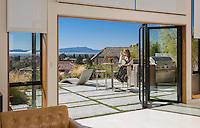 Margarido House, Oakland, California - LEED. Sliding glass doors opening living sunny room to patio overlooking San Francisco Bay