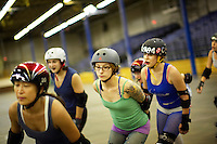 Pussy Venom (in green) and Claire D. Way (behind with 1984 helmet), skate with teammates during a roller derby practice in Wilmington, Massachusetts. Roller derby is an American contact sport, popular with young women, which combines both athleticism and a satirical punk third-wave feminism aesthetic.