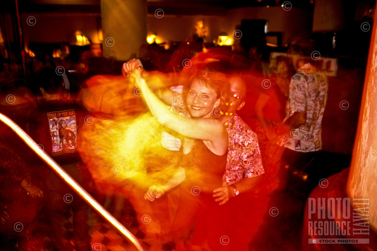 Woman in red dress, swing dancing at a nightclub in the Ala Moana Hotel, Waikiki, Oahu, Hawaii