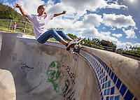 A blonde female skateboarder grinds the coping at the Banzai Skate Park on the North Shore of O'ahu