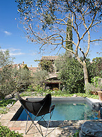 A contemporary black folding deck chair sits by the plunge pool with views towards the house